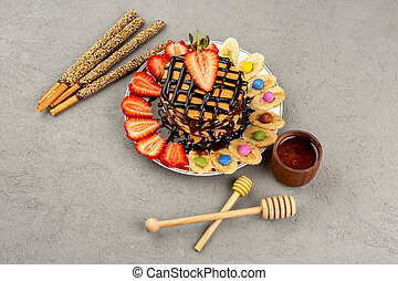 a top view yummy pancakes choco pancakes with red sliced straweberries and bananas inside white plate on the grey background