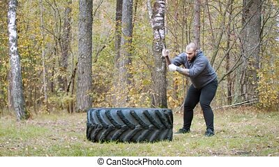A tough man bodybuilder hitting the truck tire with a metal hammer - autumn forest. Mid shot