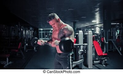 A tough man with gray hair bodybuilder pulls a barbell in the dark gym