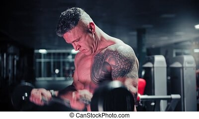 A tough man with gray hair bodybuilder pulls a barbell in the gym