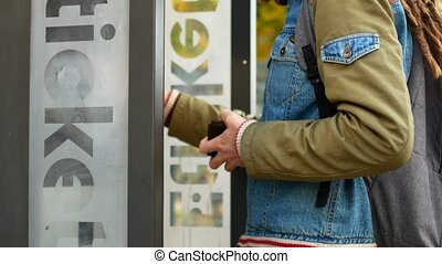 A tourist buys a ticket for public transport bus or subway. Hipster with dreadlocks buys a ticket in the electronic terminal
