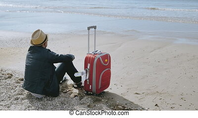 A tourist came to rest by the sea, sits on the shore with a red suitcase, copy space