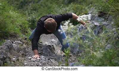 A man climbs on a rock reached the top of the cliff