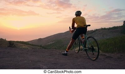 A tourist on a Bicycle admires the sunset from the top of...