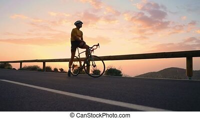 A tourist on a Bicycle admires the sunset from the top of the mountain