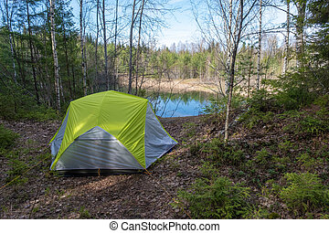 A tourist tent on the steep bank of a small forest lake on a spring day.