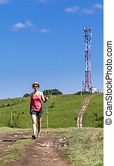 A tourist walks on the road in the background communications tower on top of a hill