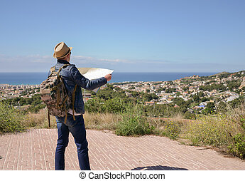 A tourist with a backpack and a hat holds a map in his hands, against the background of a city by the sea