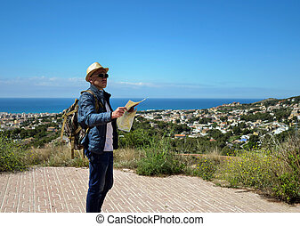 A tourist with a backpack and a map of the area in his hands stands on a mountain near the city and the sea, copyspace