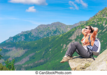 A tourist with a backpack on the background of beautiful mountains relaxes