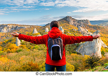A tourist with a backpack with open arms enjoying the autumn landscape in the mountains
