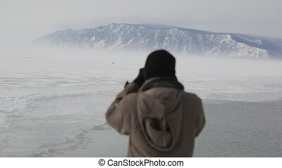 A tourist with a camera taking pictures of people on a winter lake from mountains.