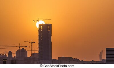 A tower in Doha timelapse, Qatar, under construction, silhouetted against the sunset.