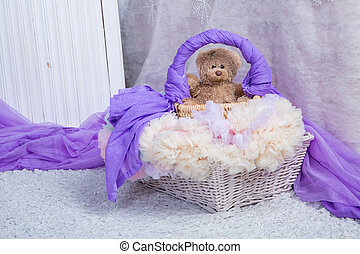 a toy bear sits in a basket in a bright room