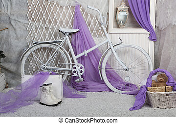 a toy bear sits in a basket in a bright room and white bike