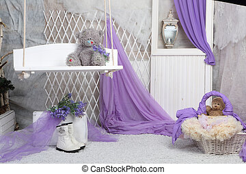 a toy bear sits on a swing in a bright room