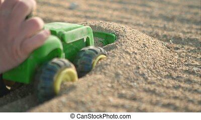A toy green truck is riding along the sand.