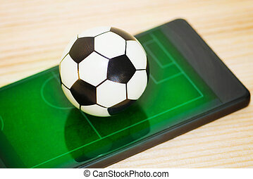 A toy soccer ball on a smartphone with a picture of a green field. Concept of the game of football.