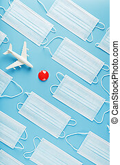 A toy white airplane and protective masks on a blue background with a red dot as the destination.
