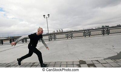 A tracer jumps street acrobatic parkour, slow-motion,...