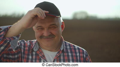 A tractor driver after plowing looks at the camera after a working day at sunset