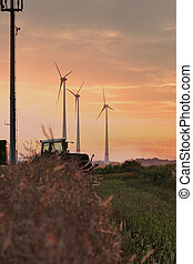 A tractor driving through a field with some wind turbines in the near distance