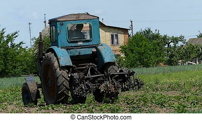 A tractor harrows the agro field in a village in late summer...