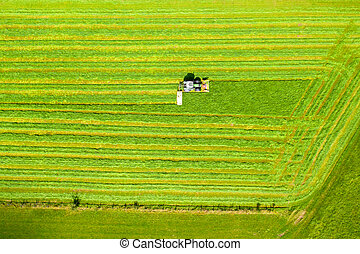 a tractor mows a field from above