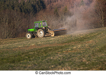 a tractor on a meadow in the evening