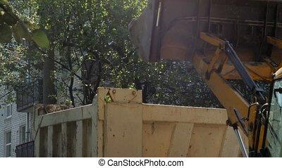 A tractor removes construction debris in the courtyard of a...