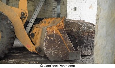 A tractor with a huge bucket in front pushes the cobblestone to the exit of the hangar, a large stone moves in space