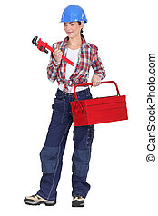 A tradeswoman holding a pipe wrench and toolbox
