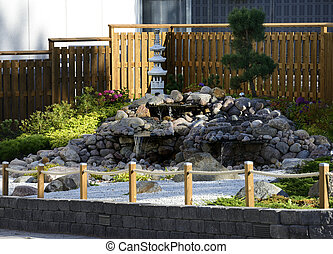 a traditional Japanese garden at the entrance to a supermarket car park in Finland