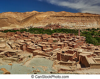 A traditional Moroccan village, small clay houses with flat roofs in the middle of a mountain valley.