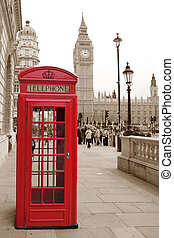 A traditional red phone booth in London with the Big Ben in a sepia background