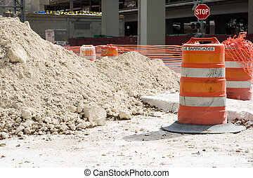 A traffic barricade of orange barrels indicates a site of road construction work with pile of sand and road sign