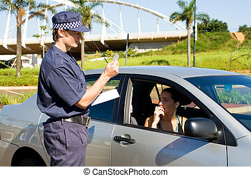 traffic cop - a traffic cop writing a ticket for a traffic ...