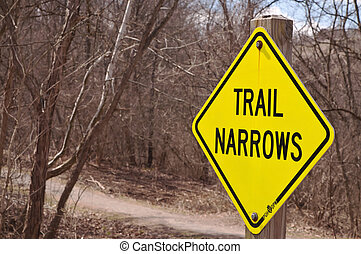 """A """"TRAIL NARROWS"""" sign in the woods"""
