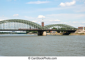 A train crosses the Hohenzollernbruecke (Hohenzollern Bridge) over the Rhine in Cologne, Germany. Beyond stands the Messeturm and to the right a monument to Kaiser Wilhelm.