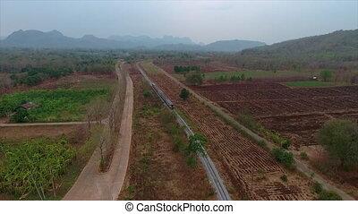 A train running on a railway track close to a farm land - A...