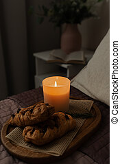 A tray of food on the bed in the bedroom. Romantic candlelight dinner. A cozy evening with candles.