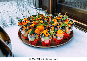 A tray with glasses with colorful slices of fruit in glasses .