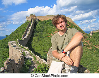A trekker man having some rest on the Great Wall of China -...