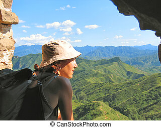 A trekker woman with a hat looking over the mountains and the jungle from the Great Wall of China, China