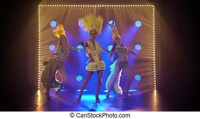 A trio of fiery female dancers dance in Brazilian carnival ...