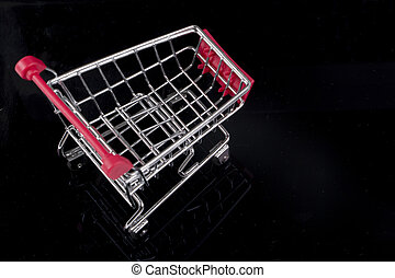 A trolley on black background. Shopping concept.