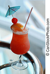 A tropical fruit drink with cherry, orange and a blue umbrella.