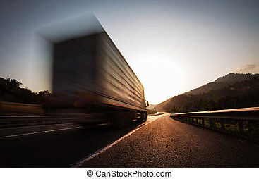 A truck is driving down the highway at sunset.
