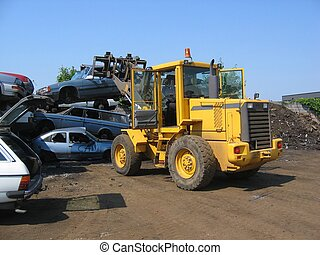 A truck lifting a car wreck at a scrapyard in Norway