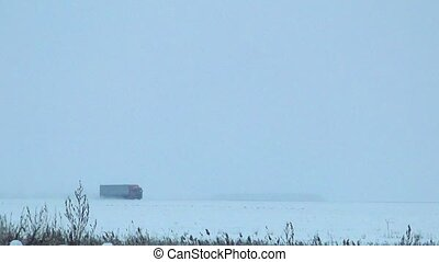 A truck with red cabin and a large van quickly goes on snow-covered road left to right